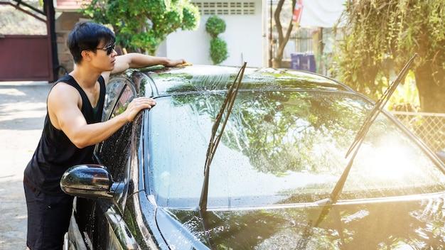 Mann, der das schwarze auto wäscht.