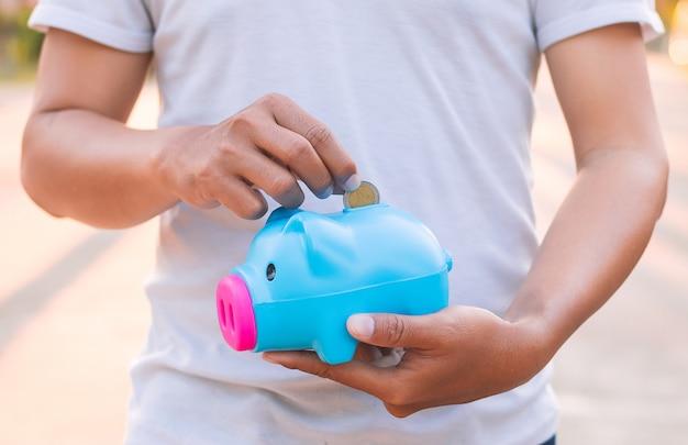 Mann, der das sparschwein, geldkonzept sparend hält.