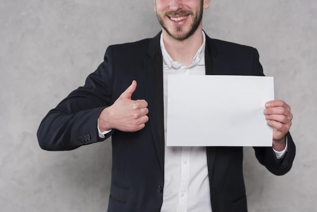 Mann, der daumen aufgibt und leeres papier hält