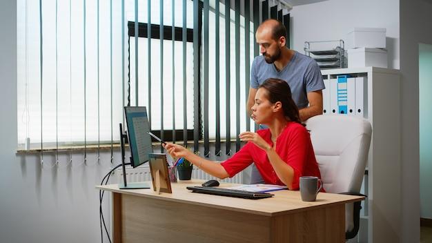 Mann, der dem hispanischen kollegen vor dem pc die lösung des problems erklärt. team, das an einem professionellen arbeitsplatz in einem persönlichen unternehmensunternehmen arbeitet, das auf der computertastatur tippt und auf den desktop zeigt