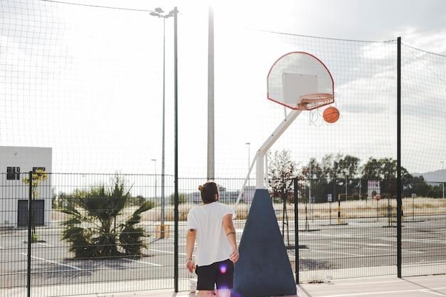 Mann, der den basketball durchläuft band betrachtet