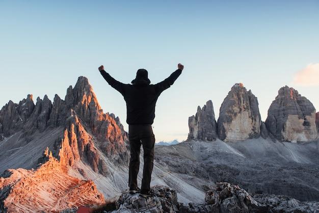 Mann, der den hügel erobert und hände zeigt, während er auf dem stein vor paternkofel und tre chime bergen steht