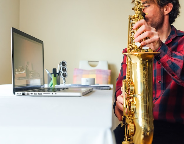 Mann, der den laptop betrachtet und spielt, während er seinen saxophon-online-kurs beobachtet