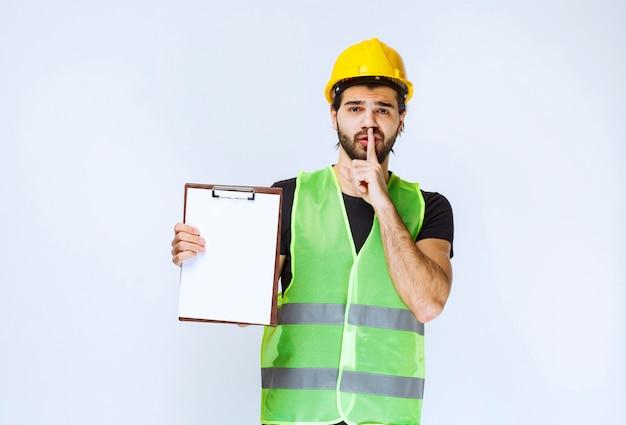 Mann, der den projektordner zeigt und um stille bittet.