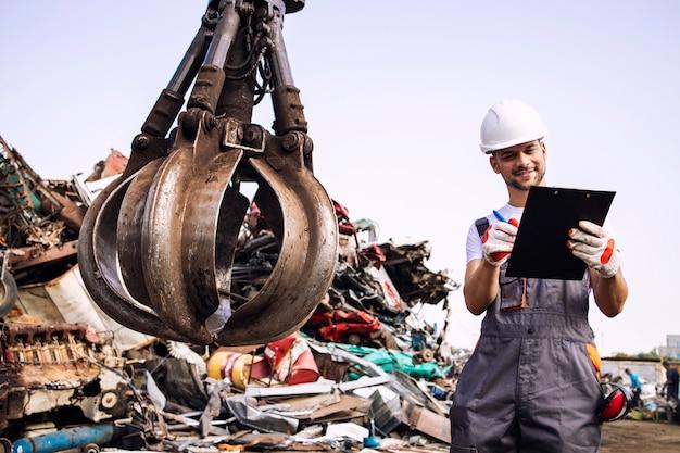 Mann, der den prozess des industriellen schrottrecyclings auf dem schrottplatz kontrolliert.