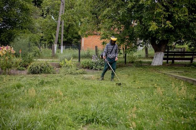 Mann, der den rasen in seinem garten mäht. gärtner schneidet das gras. lebensstil.