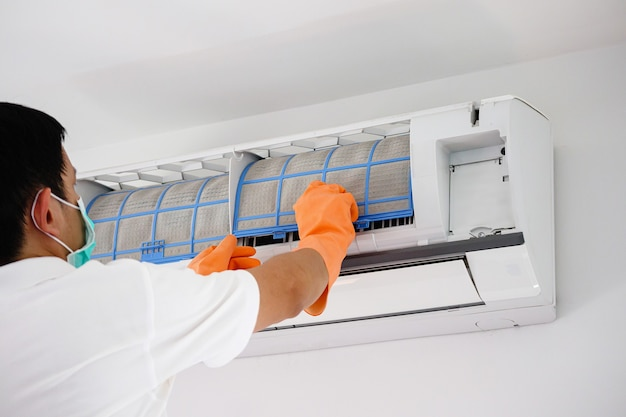 Mann, der den schmutzigen filter der klimaanlage reinigt