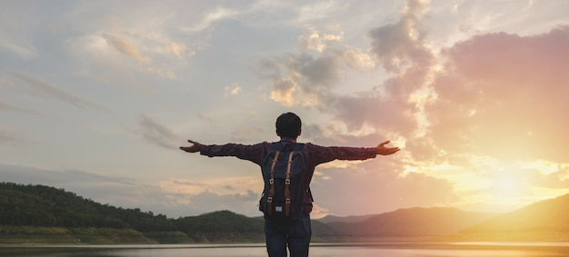 Mann, der den sonnenuntergang mit den offenen armen steht und aufpasst