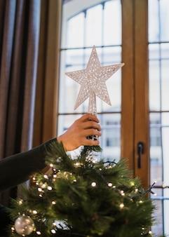 Mann, der den stern an der spitze des weihnachtsbaums anordnet