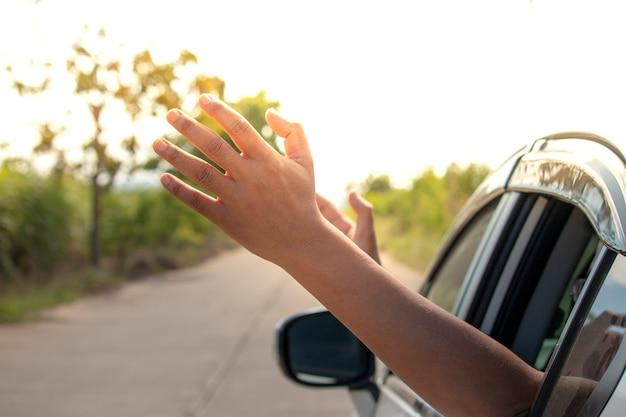 Mann, der den wind durch seine hände beim fahren in die landschaft glaubt.