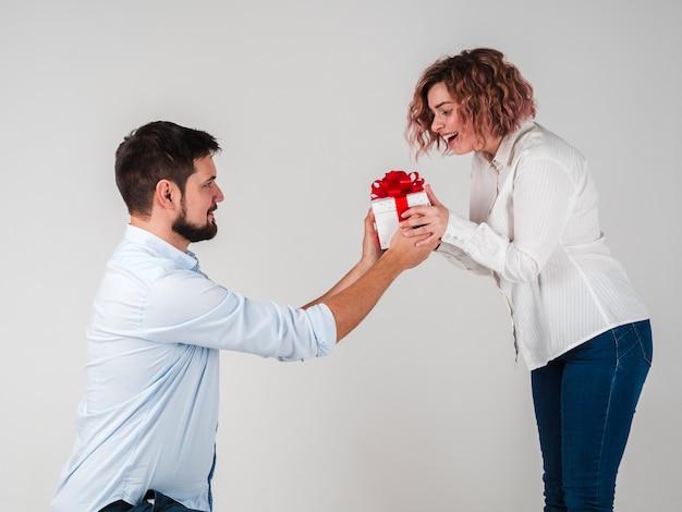 Mann, der der frau geschenk für valentinsgrüße gibt