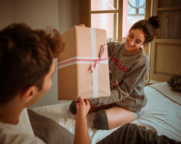Mann, der der frau geschenkbox gibt