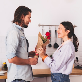 Mann, der der frau in der küche blumenstrauß der roten rosen gibt
