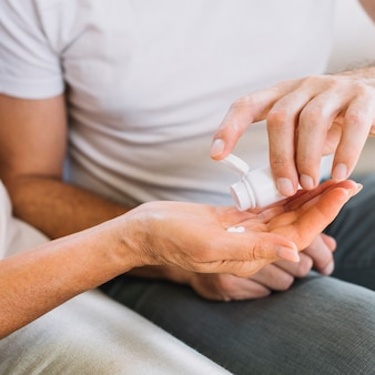 Mann, der der hand der älteren frau pillen gibt
