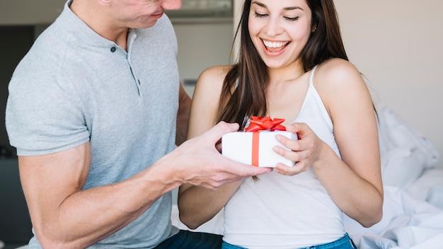 Mann, der der jungen frau geschenkbox gibt