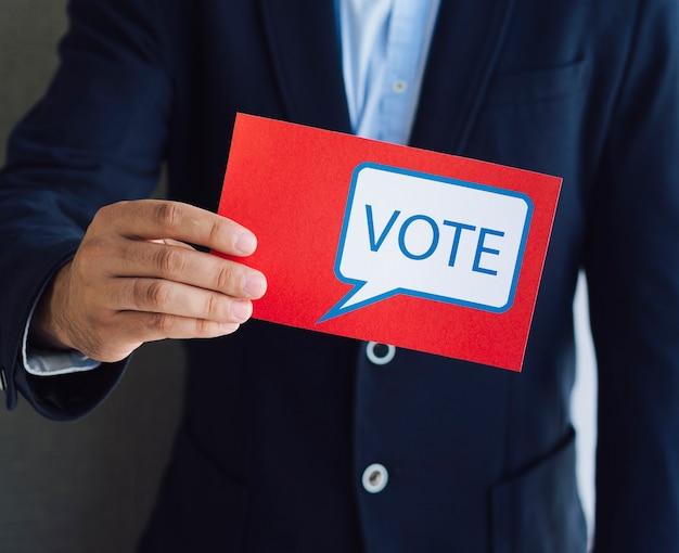 Mann, der der kamera einen roten stimmzettel zeigt