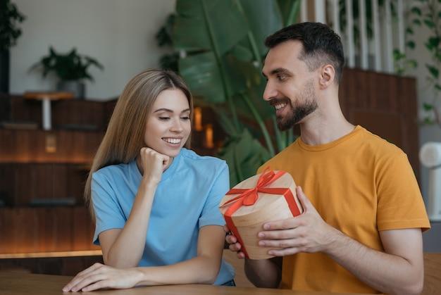 Mann, der der schönen frau geschenk dox gibt. schönes paar, das zusammen im café sitzt, romanisches datum. valentinstag konzept