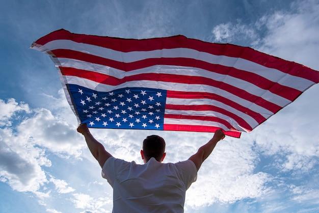 Mann, der die amerikanische usa-flagge in den händen in den usa, konzeptbild winkend hält
