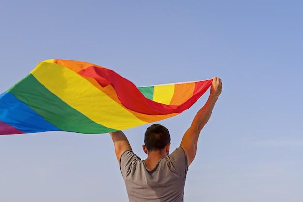 Mann, der die angehobenen hände wellenartig bewegen der lgbt-regenbogenflagge hält