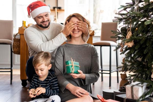 Mann, der die augen seiner frau für eine weihnachtsüberraschung bedeckt