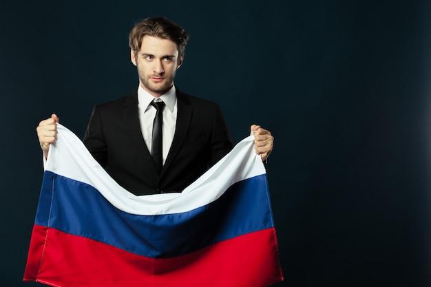 Mann, der die flagge von russland hält
