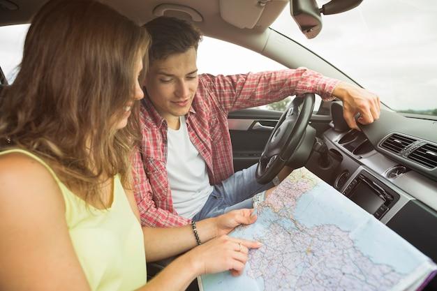 Mann, der die frau zeigt finger auf standortnavigationskarte im auto betrachtet