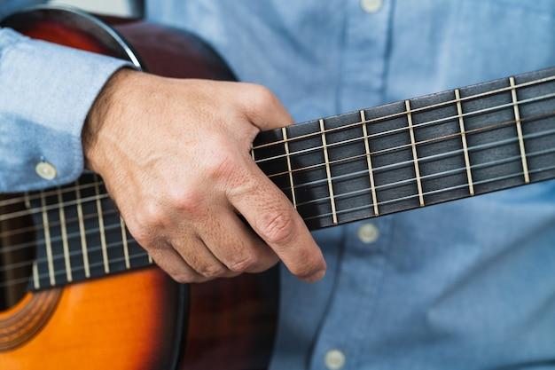 Mann, der die gitarre aufhebt. lernen mit einem online-kurs