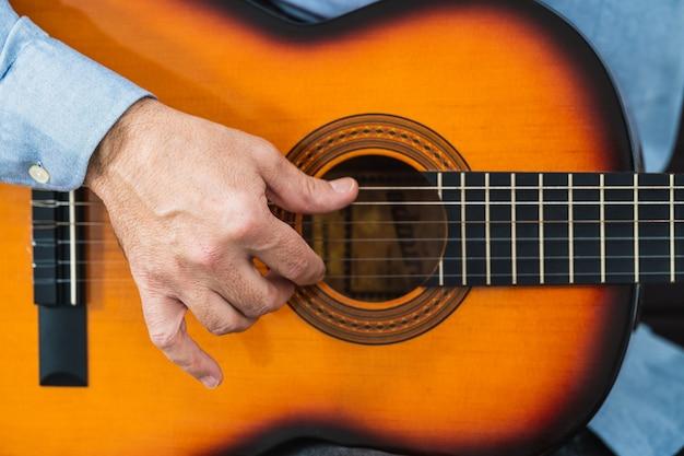 Mann, der die gitarrensaiten spielt. üben und lernen mit einem online-kurs