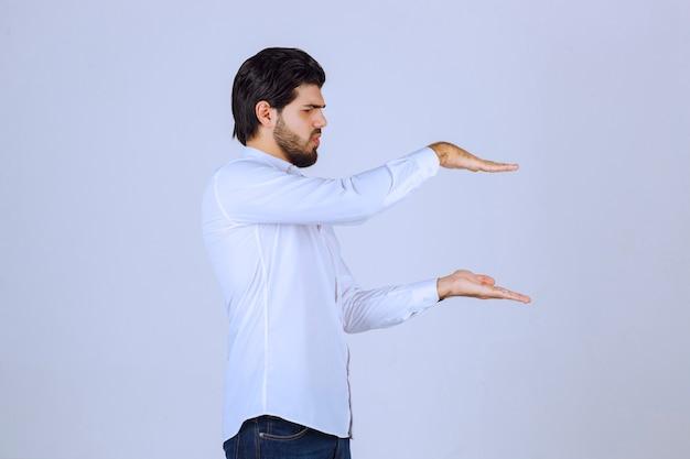 Mann, der die größe eines objekts zeigt.