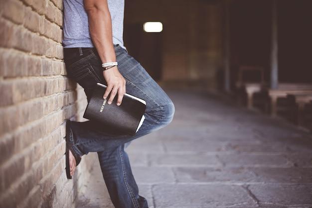 Mann, der die heilige bibel hält, die auf gemauerte wand stützt