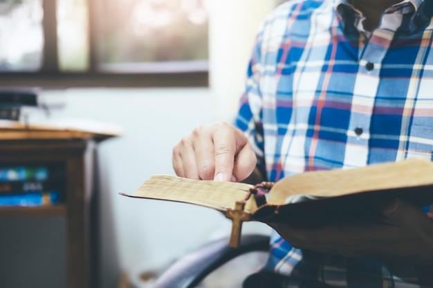 Mann, der die heilige christliche bibel hält und liest