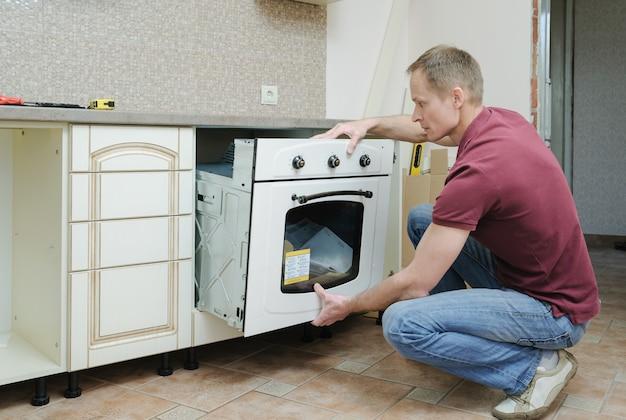 Mann, der die installation des eingebauten elektrischen ofens tut.