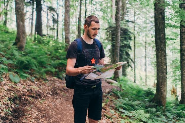 Mann, der die karte beim wandern im wald betrachtet