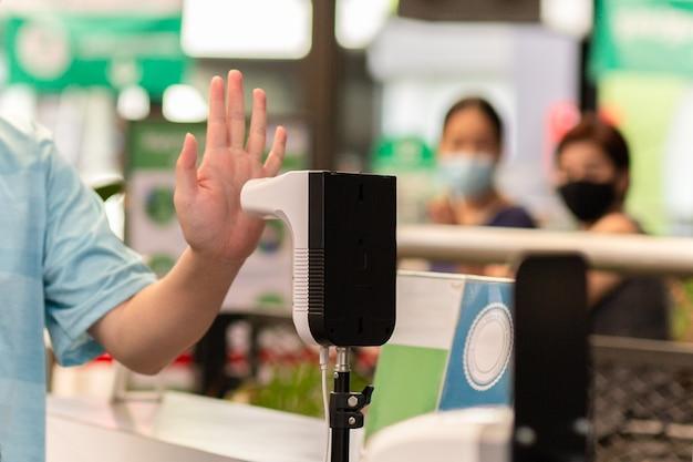 Mann, der die körpertemperatur durch infrarot-digitalthermometer mit seiner hand überprüft