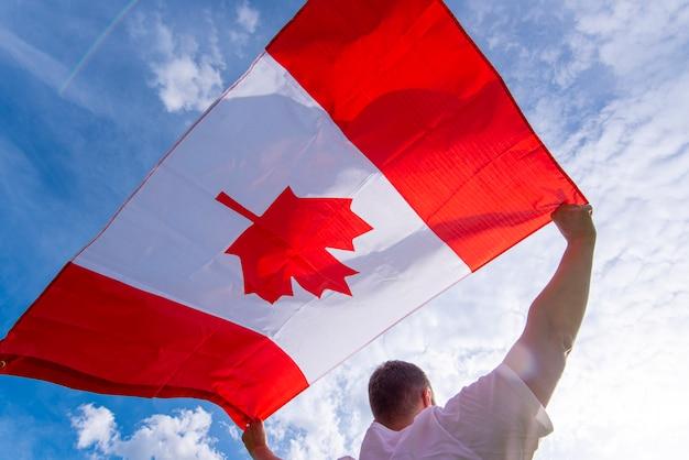 Mann, der die nationalflagge von kanada gegen blauen himmel hält