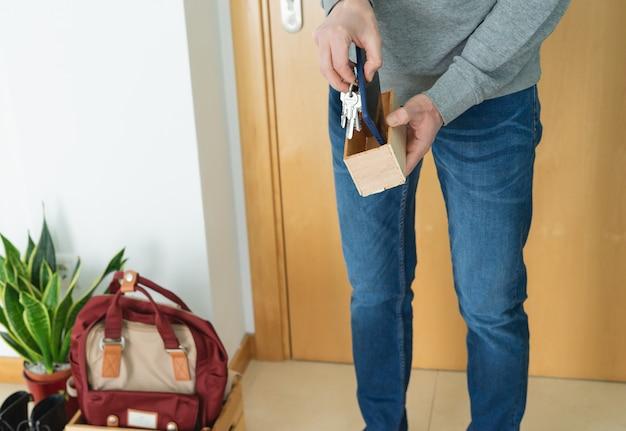 Mann, der die schlüssel, das handy, die schuhe und den rucksack richtig verlässt, wenn er nach hause kommt. konzept covid-19. coronavirus.