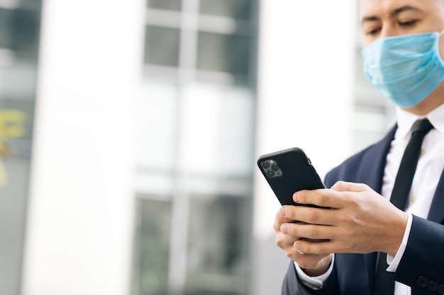 Mann, der die schützende gesichtsmaske in der straße betrachtet, die die soziale medien-app des smartphones surft Premium Fotos