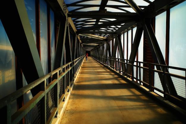 Mann, der die stadtbrücke während des sonnenuntergangzeithintergrundes überquert