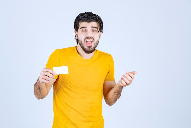 Mann, der die visitenkarte eines partners erhält und verwirrt wird.