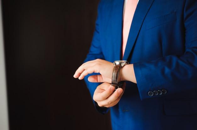 Mann, der die zeit auf seiner armbanduhr überprüft