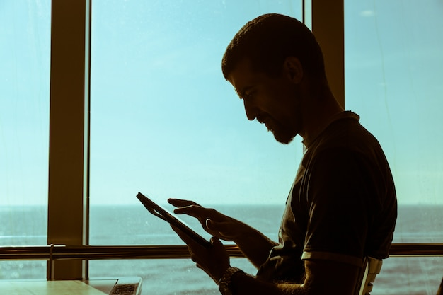 Mann, der digital-tablet auf einer fähre verwendet
