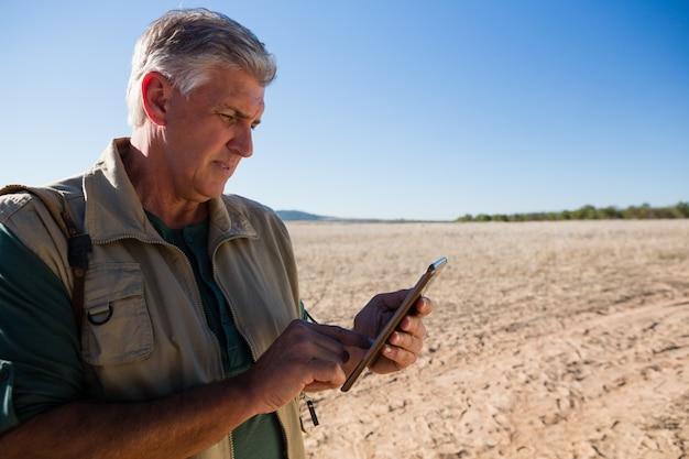 Mann, der digitale tablette auf landschaft verwendet