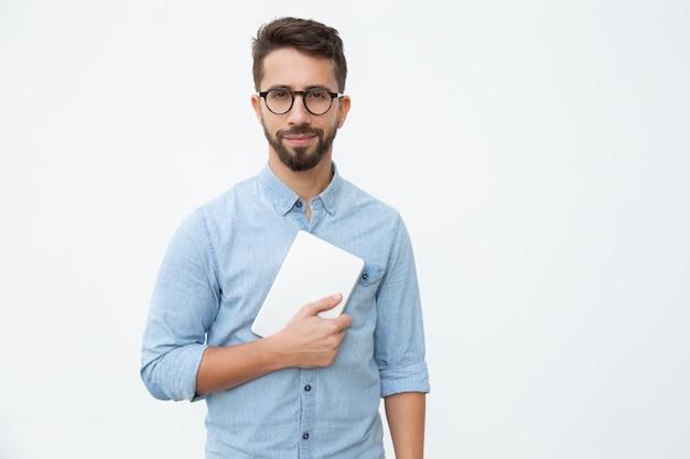 Mann, der digitale tablette hält und an der kamera lächelt