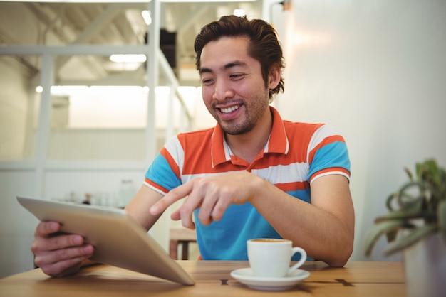 Mann, der digitale tablette mit kaffeetasse auf tisch verwendet