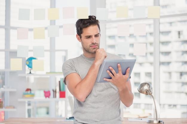 Mann, der digitale tablette und klebrige anmerkungen hält