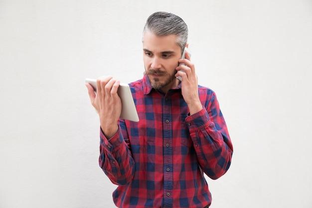 Mann, der digitale tablette verwendet und durch smartphone spricht