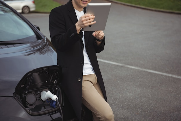Mann, der digitales tablett beim laden des elektroautos verwendet