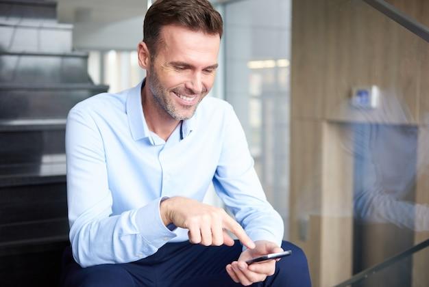 Mann, der digitales tablett im büro durchsucht
