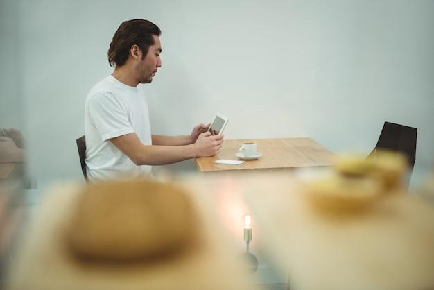Mann, der digitales tablett im kaffeehaus verwendet