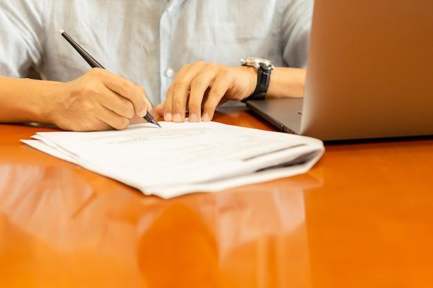 Mann, der dokumente mit federkiel und laptop auf hölzernem schreibtisch unterschreibt.